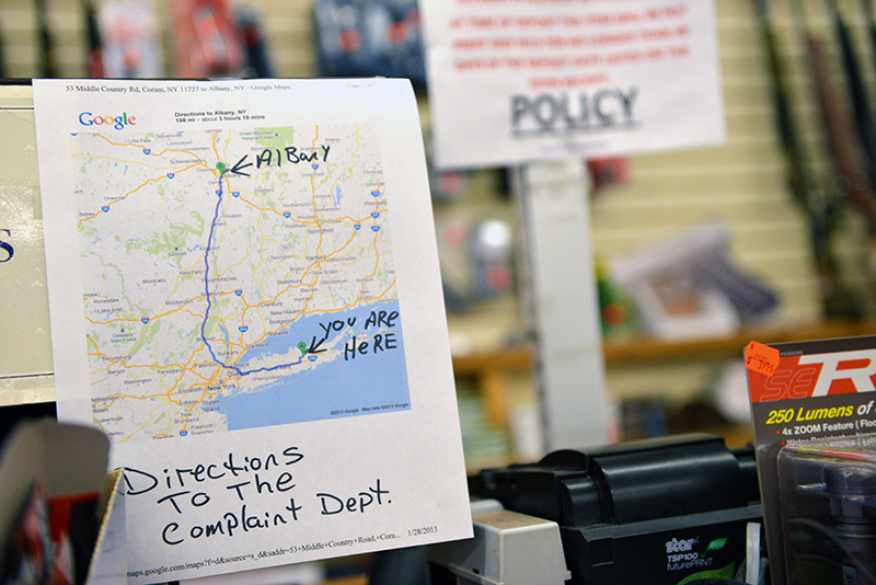 A sign that rests on the cash register in Benson's Gun Shop. An employee eventually got tired of people complaining to him about the new laws so he decided to print this out as a message to his customers and to lawmakers. Photo by Frank Posillico.